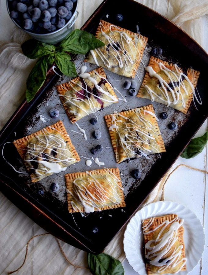 Living the Gourmet: Baked into a delicate, buttery crust, these Blueberry Basil Hand Pies are bursting with the flavors of the summer.